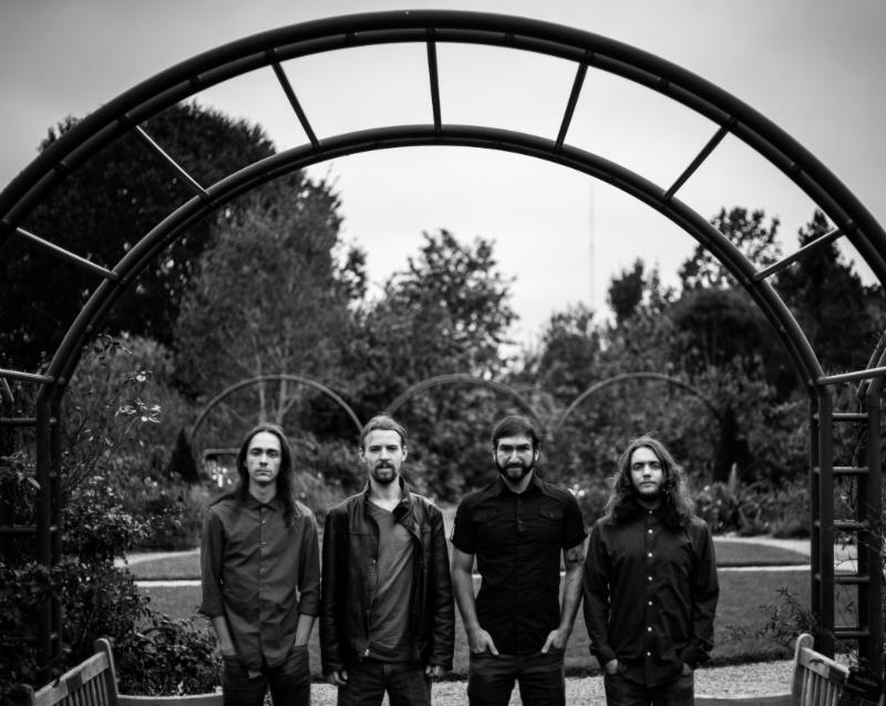 A black and white photo of the members of Anamorph standing in a park under a steel archway