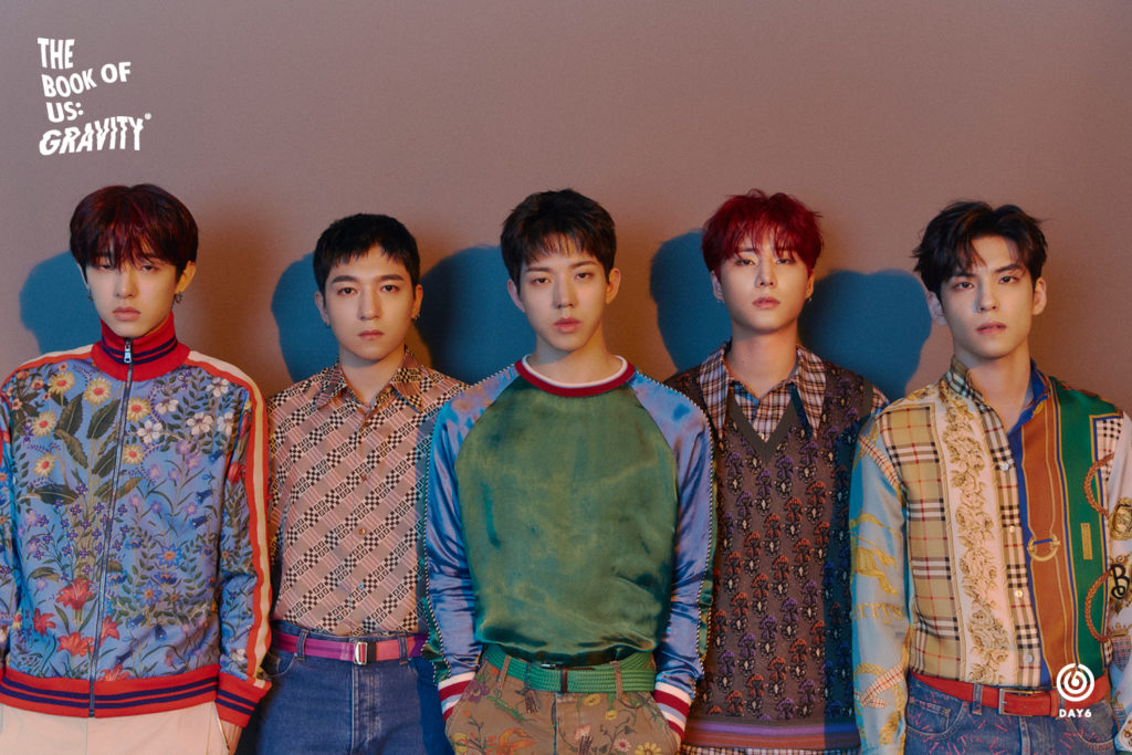 Members of DAY6 standing in front of a light purple wall with blue shadows behind each member.