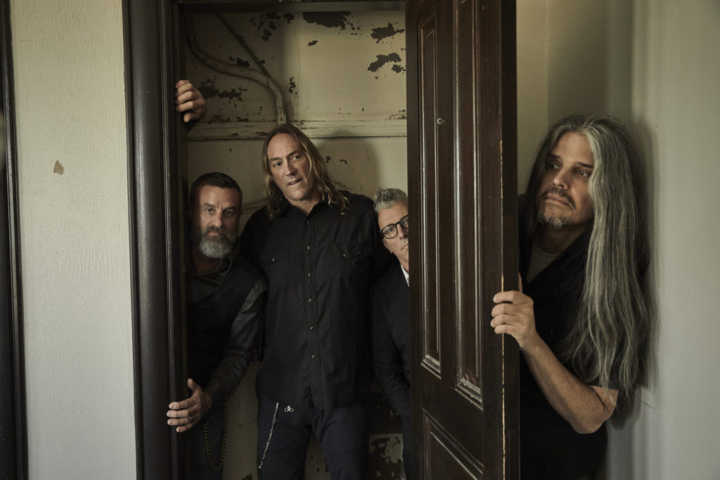Three members of Tool in a doorway with the fourth member peaking out from behind the door.